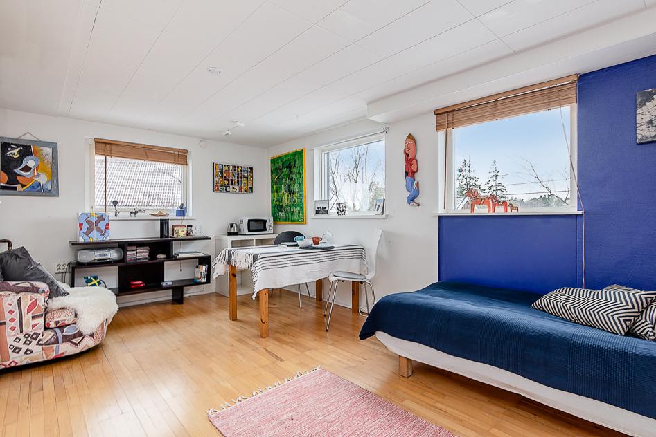Stort allrum/sovrum med tre fönster på entréplan