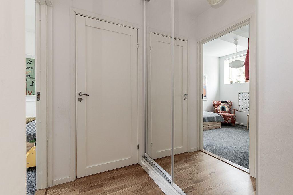 Titt via garderobernas spegeldörrar i hallen