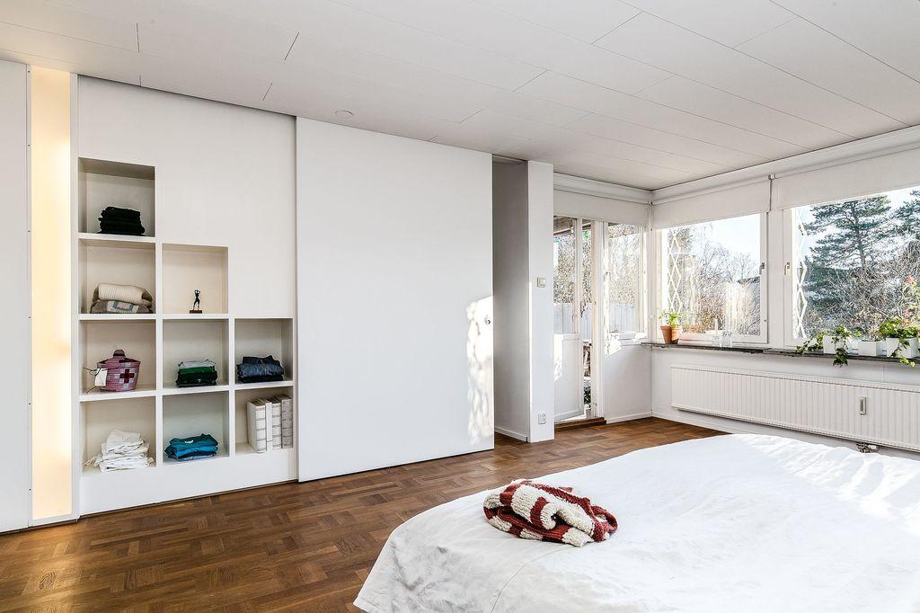 Master bedroom med inbyggda hyllor bakom skjutdörren samt inbyggd belysning