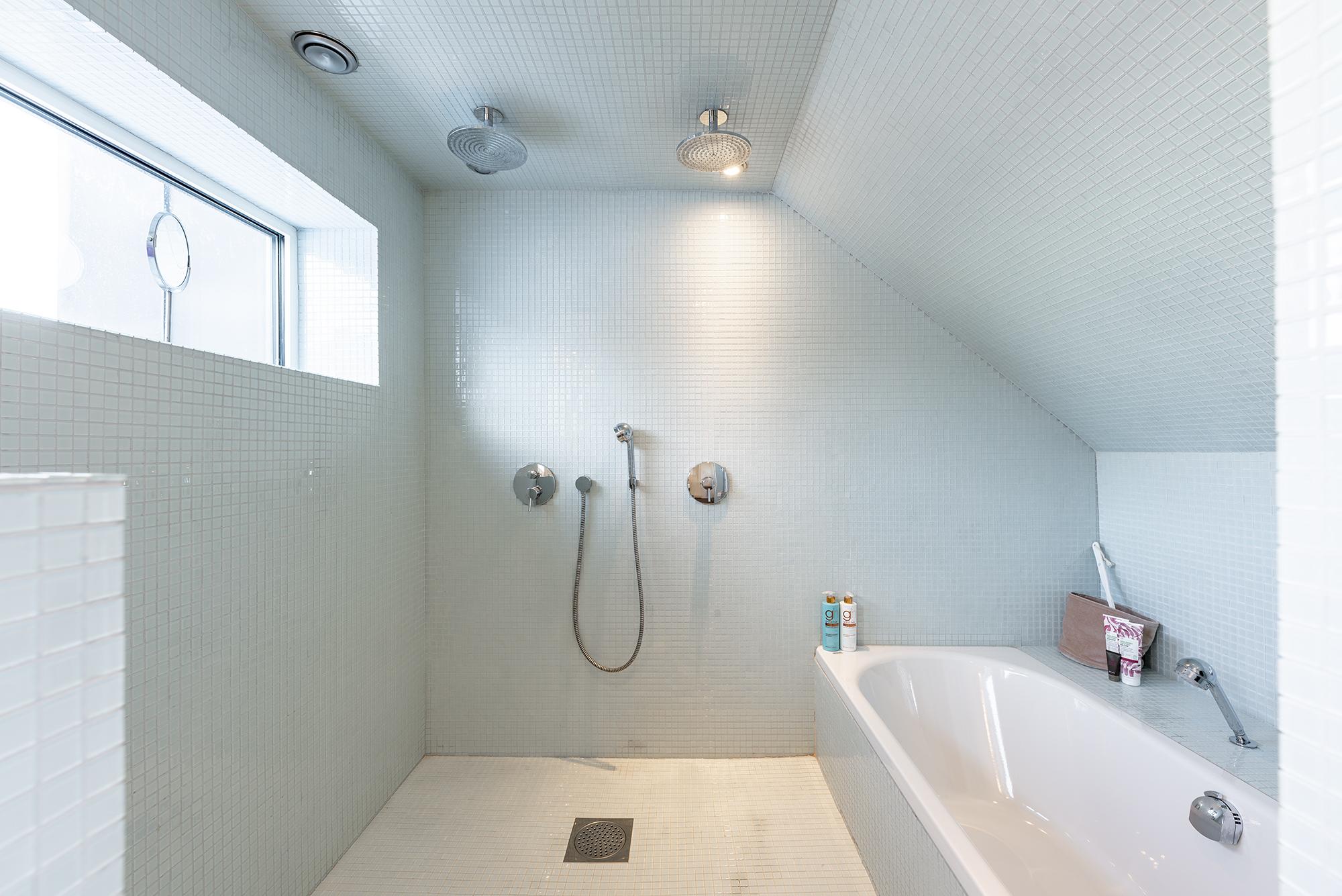 Generöst duschrum med badkar och dubbla duschar. Fönster med utsikt.