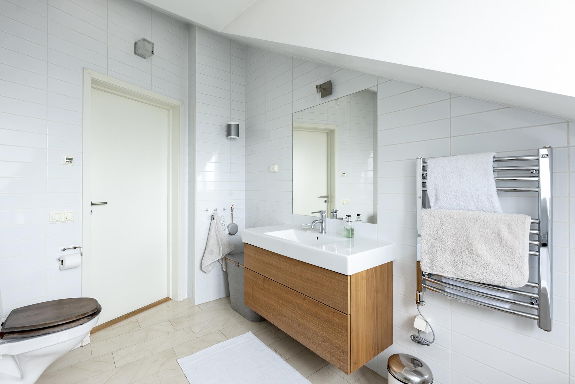 Badrum på entréplan med tvättställ med kommod från Aspen och  infälld spegel.