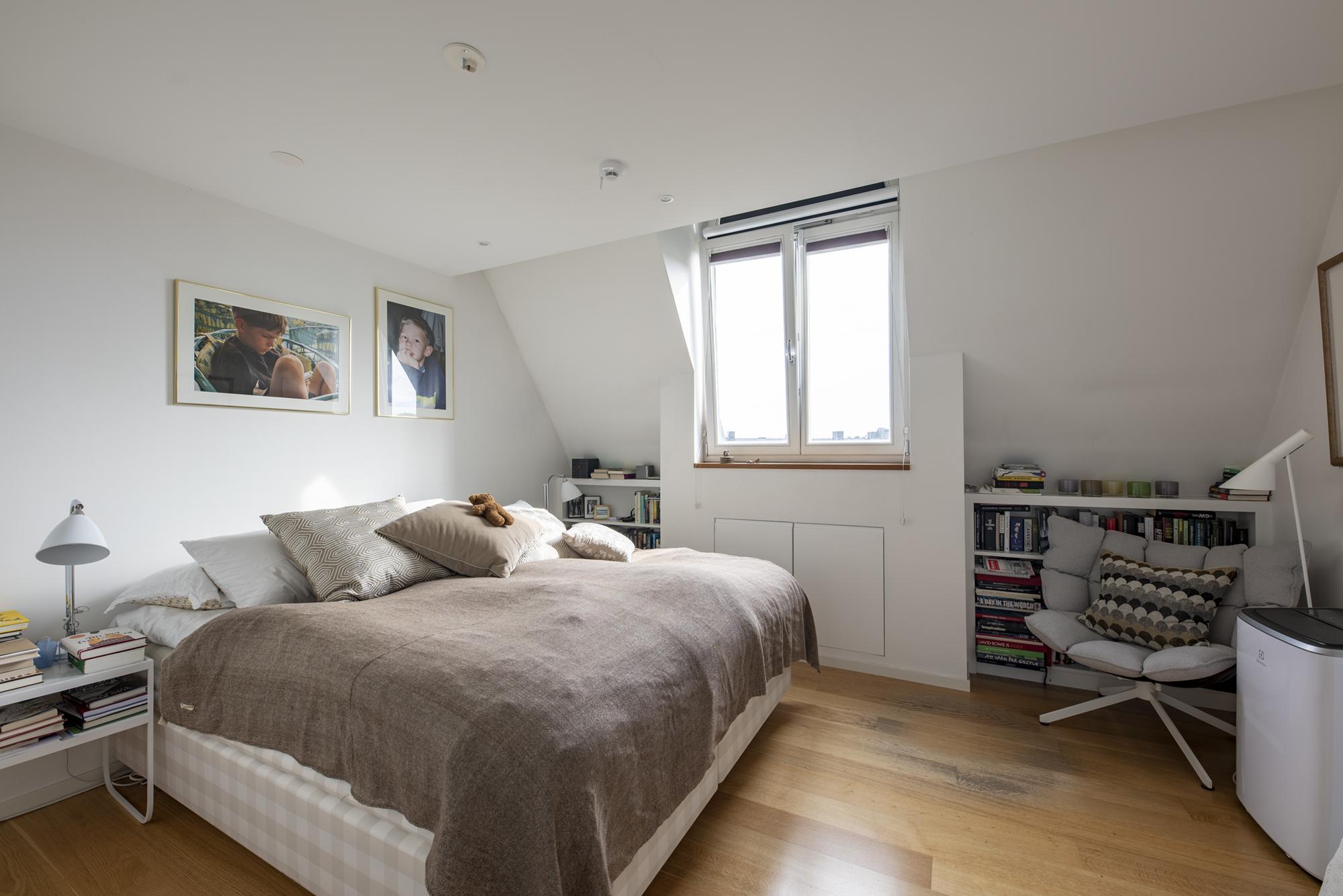 Master bedroom med platsbyggda bokhyllor och dold förvaring i kattvinden