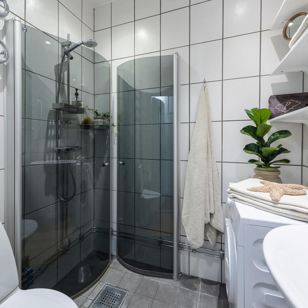 Badrum med glasad duschvägg och plats för tvättmaskin